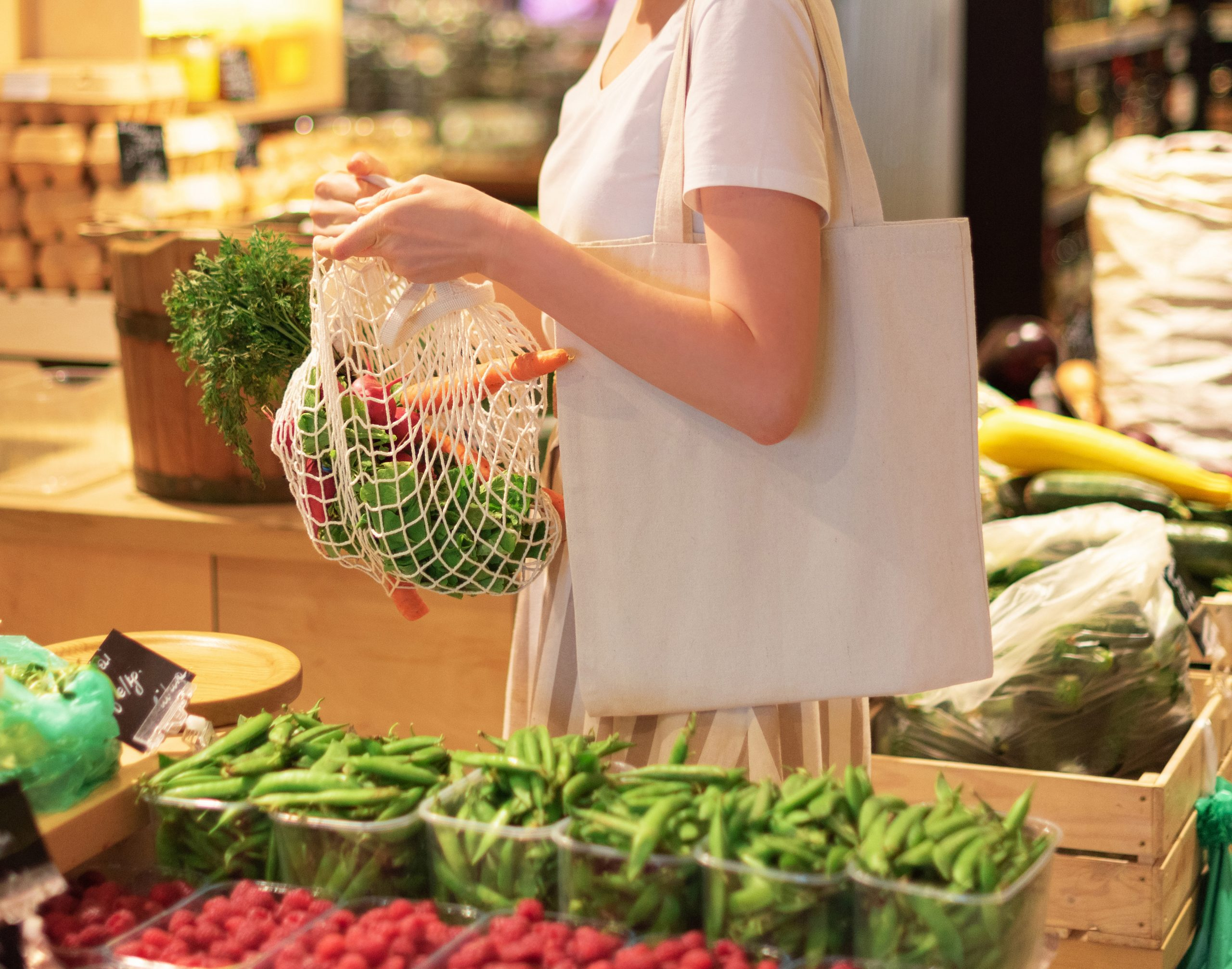 Woman chooses fruits and vegetables at farmers market. Zero waste, plastic free concept. Sustainable lifestyle. Reusable cotton and mesh eco bags for shopping.